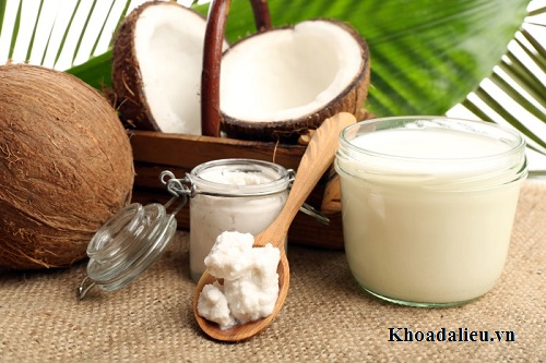 Coconut with jars of coconut oil and  milk on sackcloth on natural background